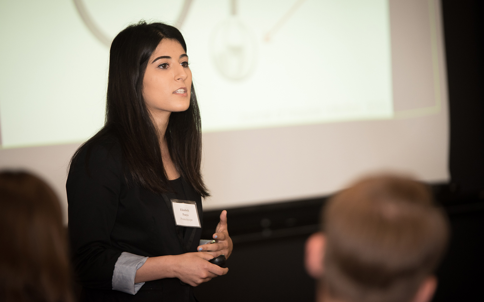 "<i>Elizabeth ""Liz'' Pouya, a rising senior majoring in physiology and neurobiology who ultimately hopes to become a physician, presents her idea to prospective investors. (Nathan Oldham/UConn School of Business)</i>"