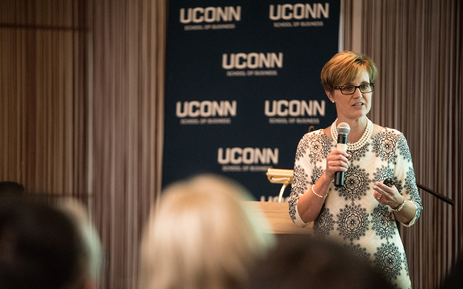 Corliss Montesi '86, vice president and corporate controller at Stanley Black & Decker, addresses hundreds of enthusiastic students at one of several graduate student Convocation events. (Nathan Oldham/UConn School of Business)