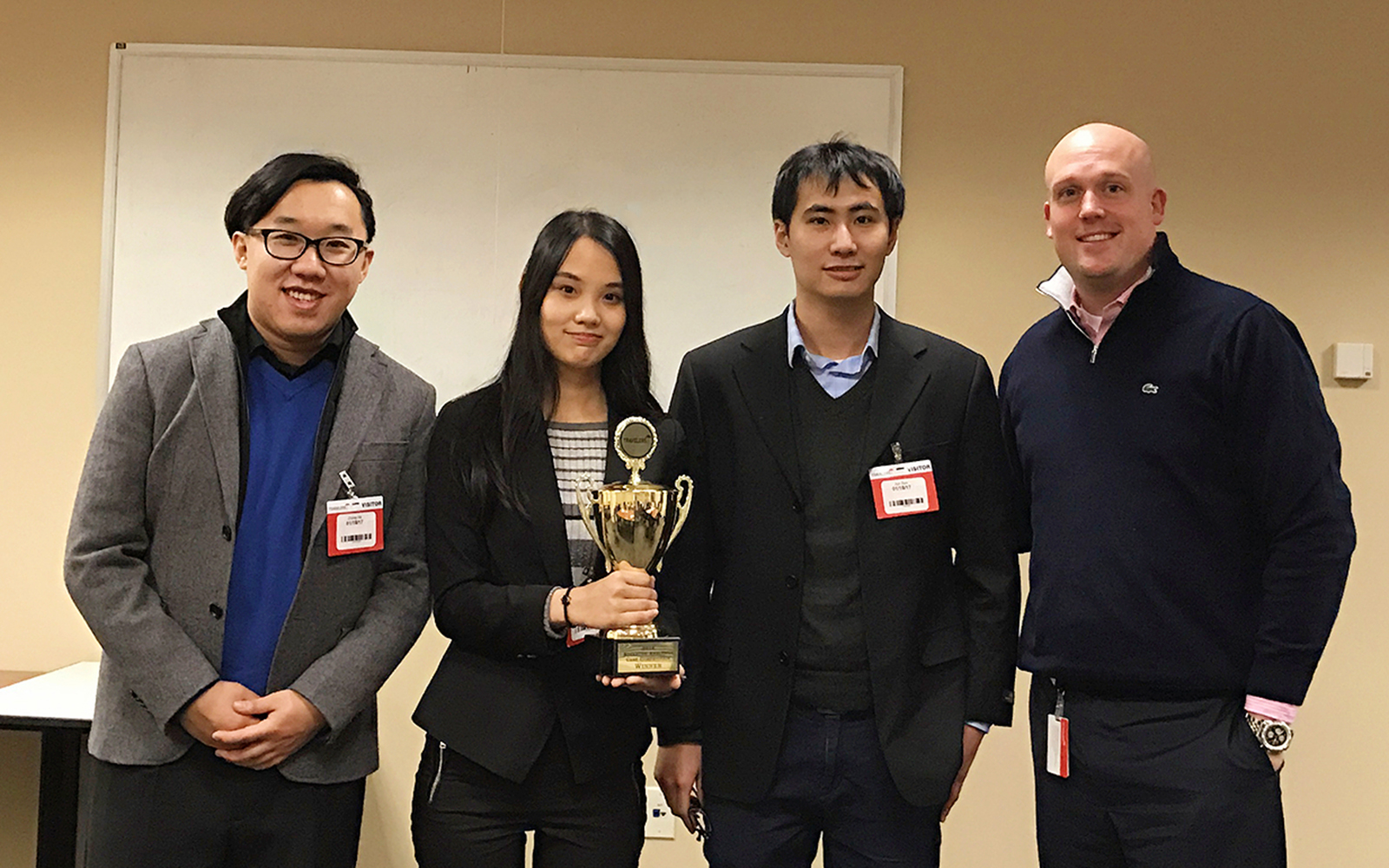 "Photo, left to right: MSBAPM students Zhong He '17, Xin ""Amy"" Ni '16, and Jun Sun '16 pose for a photo with Patrick Buckley, manager of the Advanced Analytics Leadership Development Program at Travelers, following the UConn team's victory. (Xin ""Amy'' Ni)"