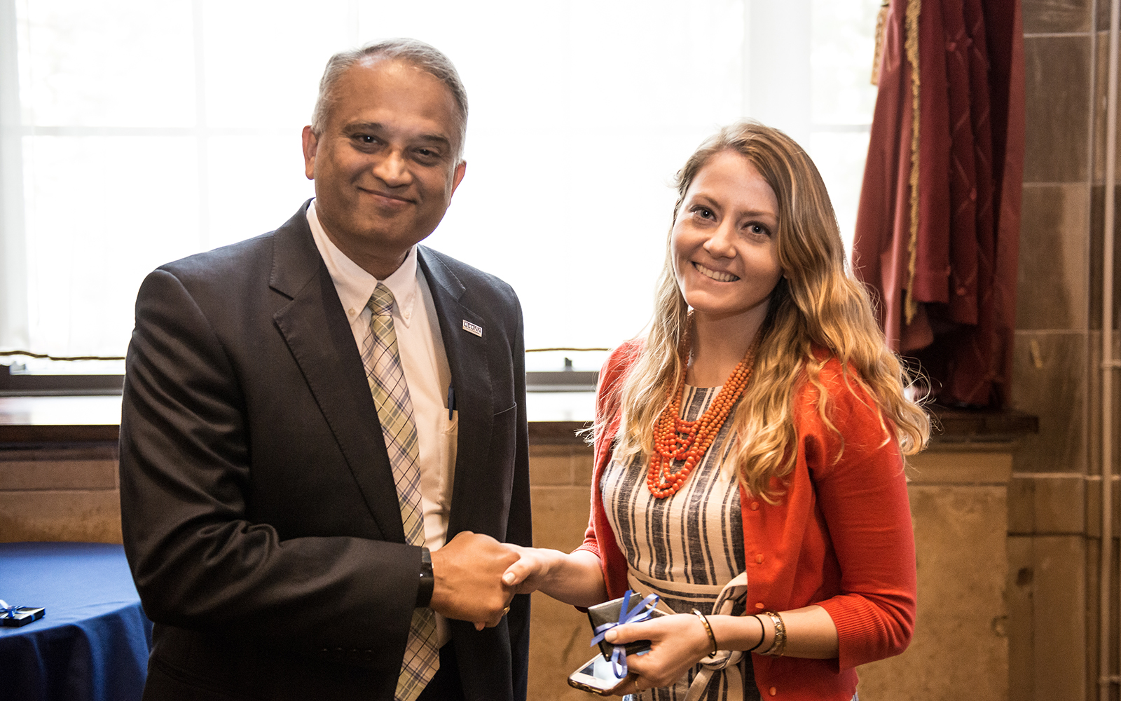 Associate Dean Suresh Nair shakes hands with Jenny Kowalski '17 MBA at the annual MBA Awards Ceremony earlier this month. (Nathan Oldham/UConn School of Business)