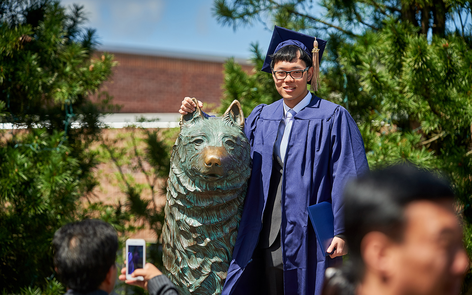 Bo Ni '17 (BUS) poses for a photo with the husky statue following the School of Business Commencement ceremony on May 7, 2017. (Peter Morenus/UConn Photo)