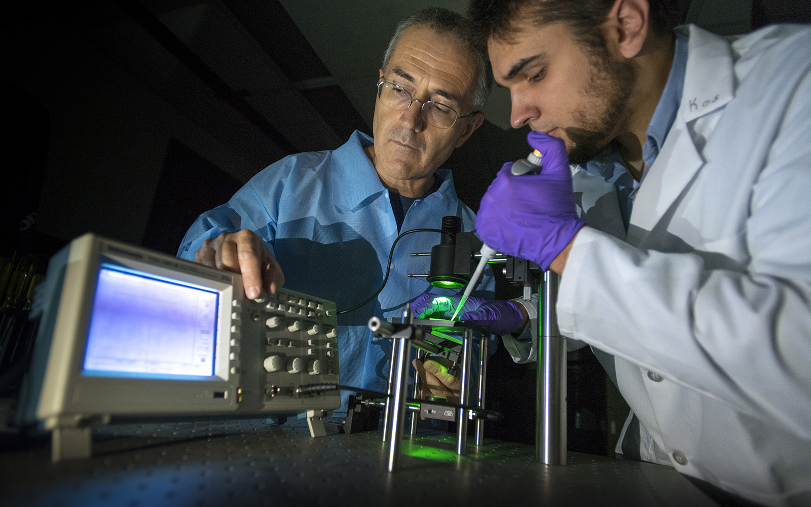 UConn engineering researchers George Lykotrafitis, left, and graduate student Kostyantyn Partola have developed a device to test an important indicator of heart health that is often ignored – blood viscosity. Here they are demonstrating the device, known as a whole blood rheometer. (Sean Flynn/UConn Photo)
