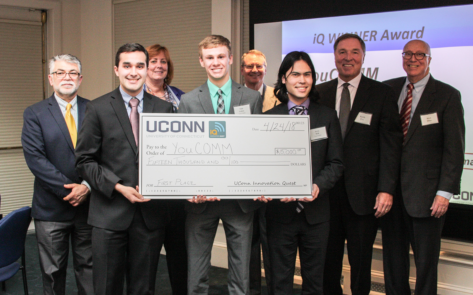 From left, Kazem Kazerounian, dean of the School of Engineering; YouCOMM co-founder Daniel Yasoshima; Lucy Gilson, head of the Management Department; YouCOMM co-founder Tom Cotton; Provost Craig Kennedy; student Jeren Koh; UConn iQ founder Keith Fox '80 and iQ Director Professor Rich Dino pose for a photo after the announcement that YouCOMM won the grand prize. (Nicolle Anderson/UConn School of Business)