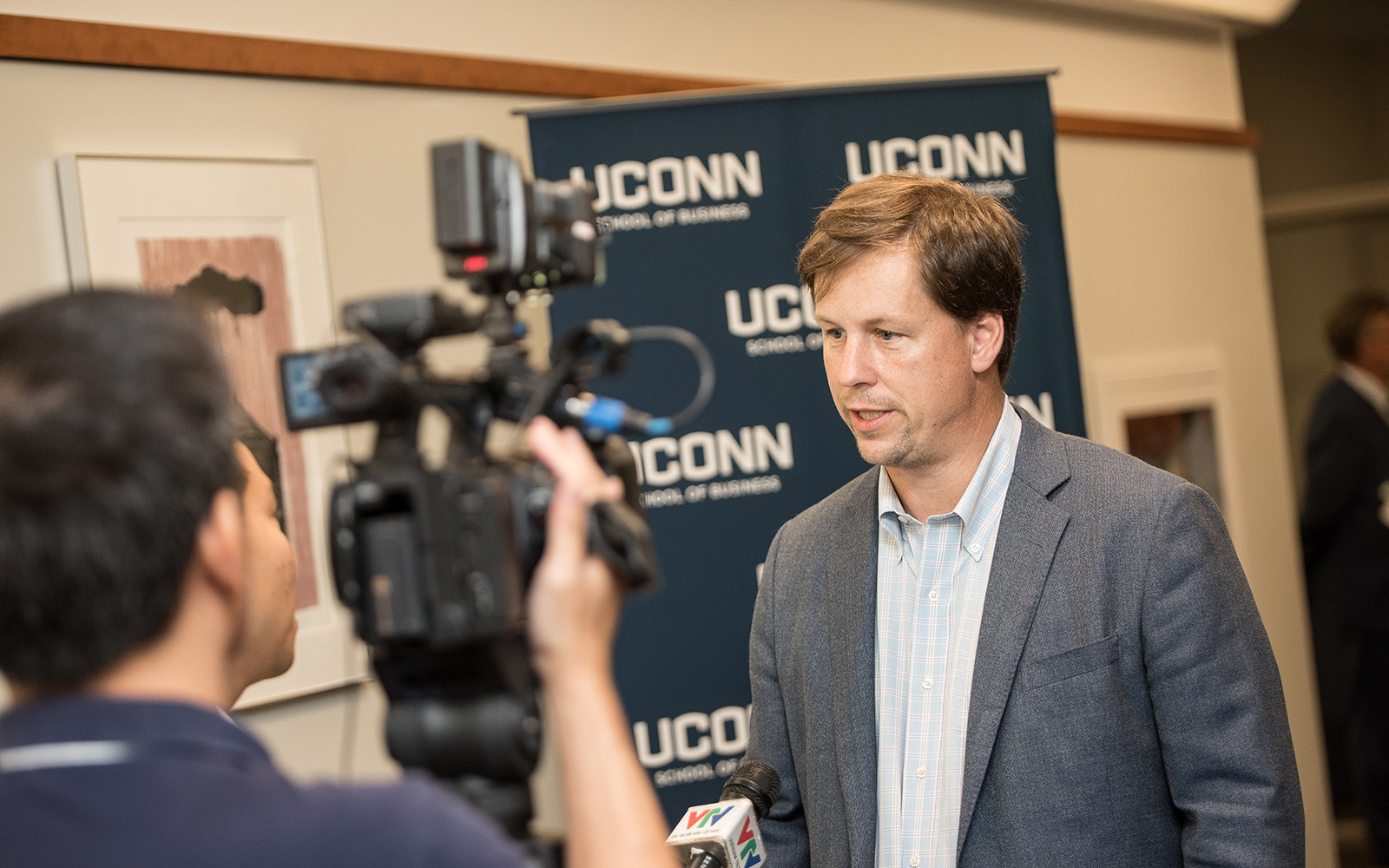 Professor David Noble, co-chair of the UConn Blockchain symposium, is interviewed by a reporter from Vietnam's state news agency. (Nathan Oldham/UConn School of Business)