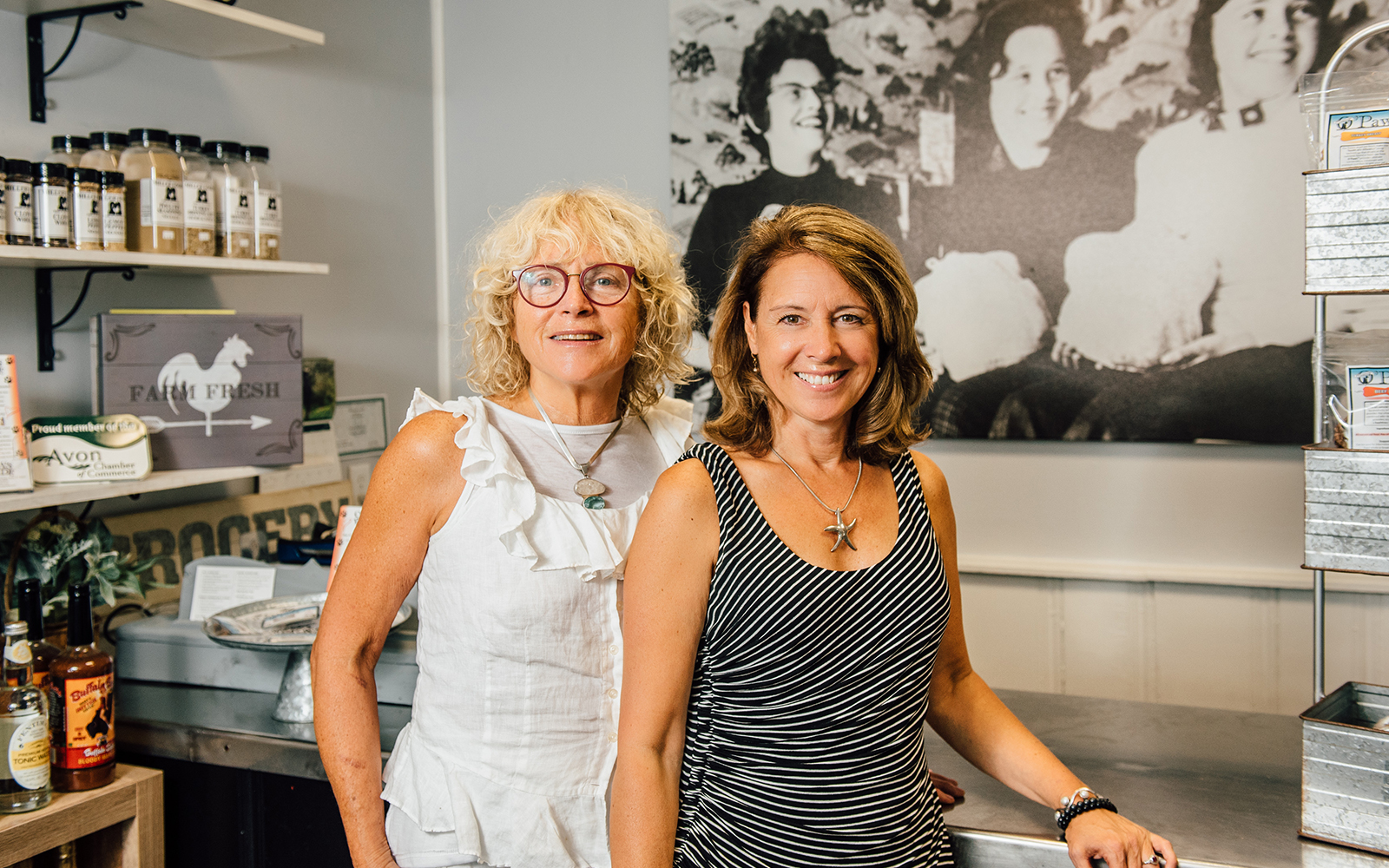 "Cal Miller-Stevens, left, and her niece Capri Frank pose for a photo inside the store at Miller Foods, Inc., a fourth-generation, family owned and operated food business located in Avon, Conn. Behind them is a photo taken in the early 1960s, in the same location. From left is family matriarch Margaret ""Oma"" Miller and her two daughters, Sandi Trudeau (Frank's mother) and Miller-Stevens. (Nathan Oldham / UConn School of Business)"