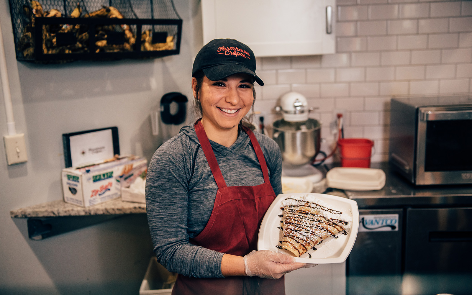 Ashley DeCarlo '19 (above) shows off her crepe-making skills at Farmhouse Crepes in Downtown Storrs. Ashley also handles their social media in addition to her regular duties, plus a job at Geezeo in Glastonbury, not to mention a full set of classes and cheerleading! (Nathan Oldham / UConn School of Business)