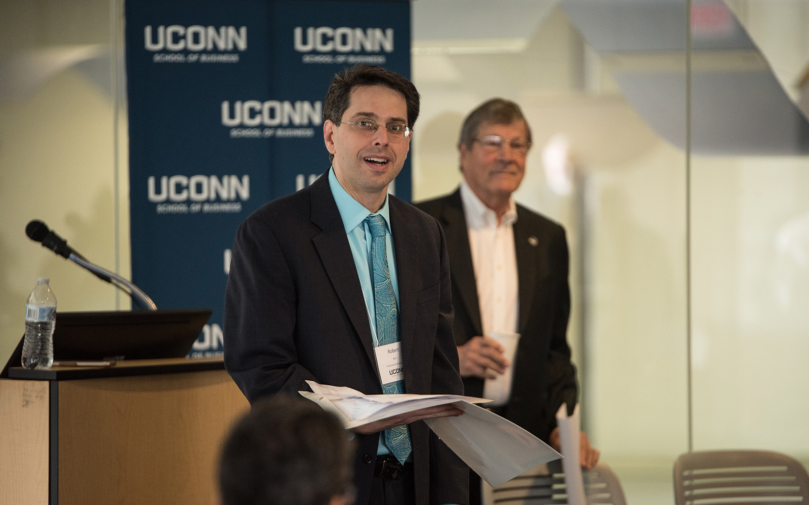 Professor Robert Bird (left) speaks during the Summit on the Academic Profession of Business Law, with Interim Provost John Elliott (Right) behind him. (Nathan Oldham / UConn School of Business)
