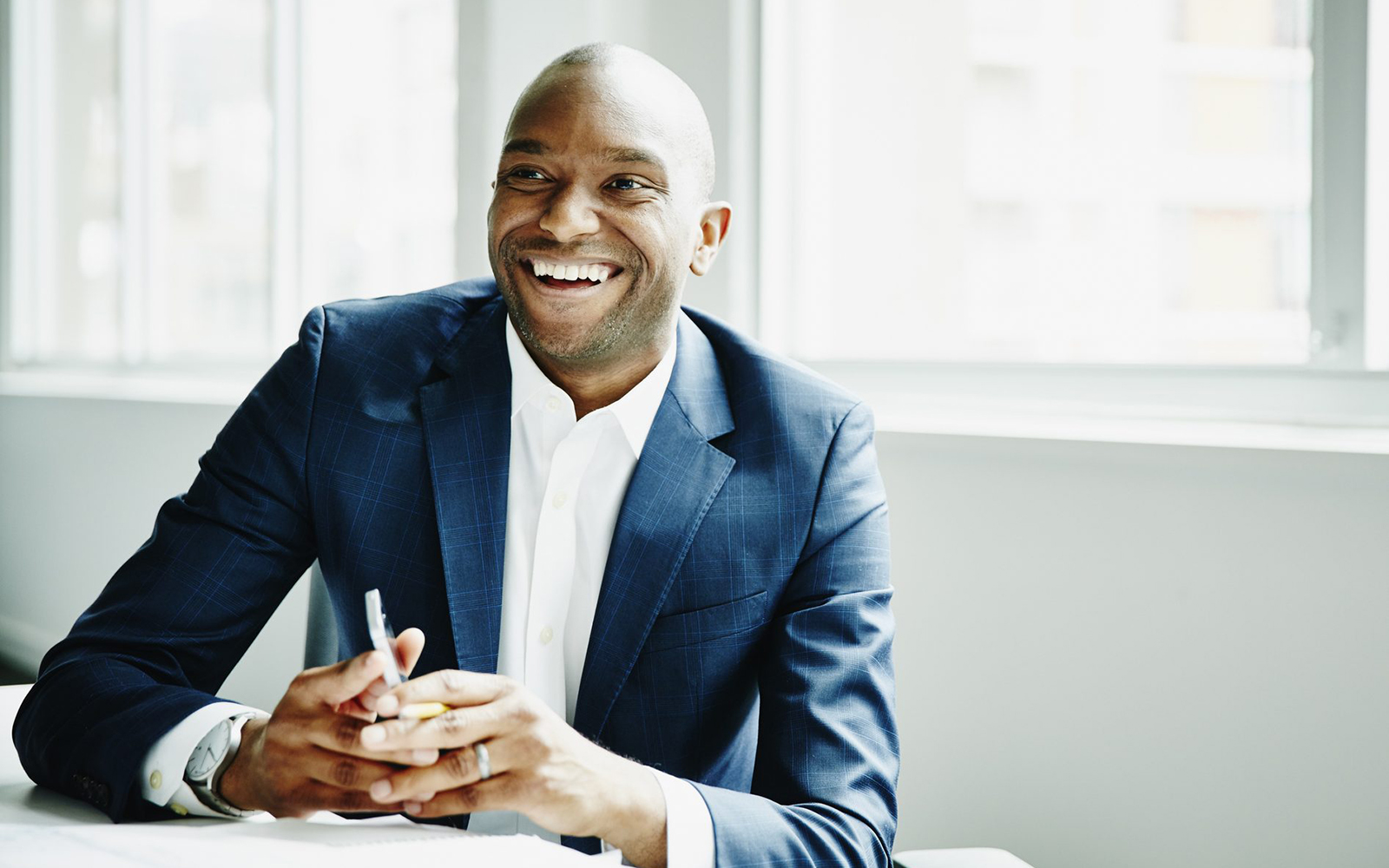 Stock photo of a man of color in a business suit, smiling.