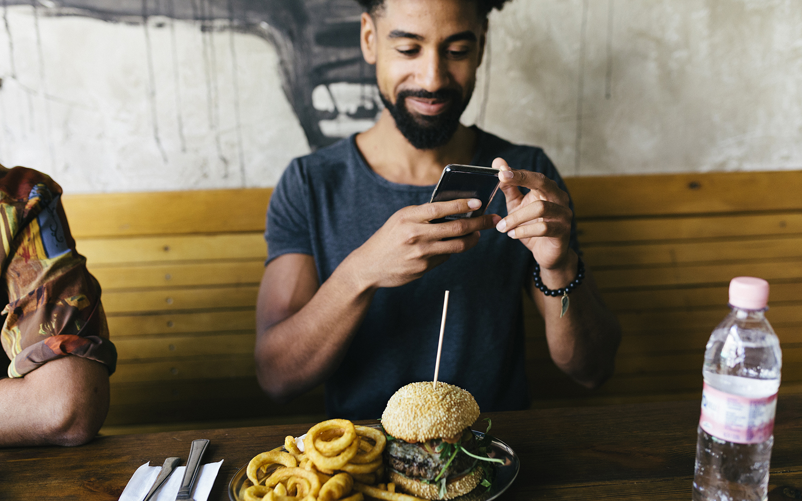 A man uses his smartphone to take photos of his burger at a restaurant. (Getty Images)