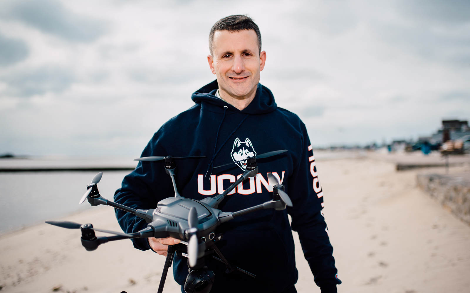 Jason Otrin poses on the beach with a drone in his hand.