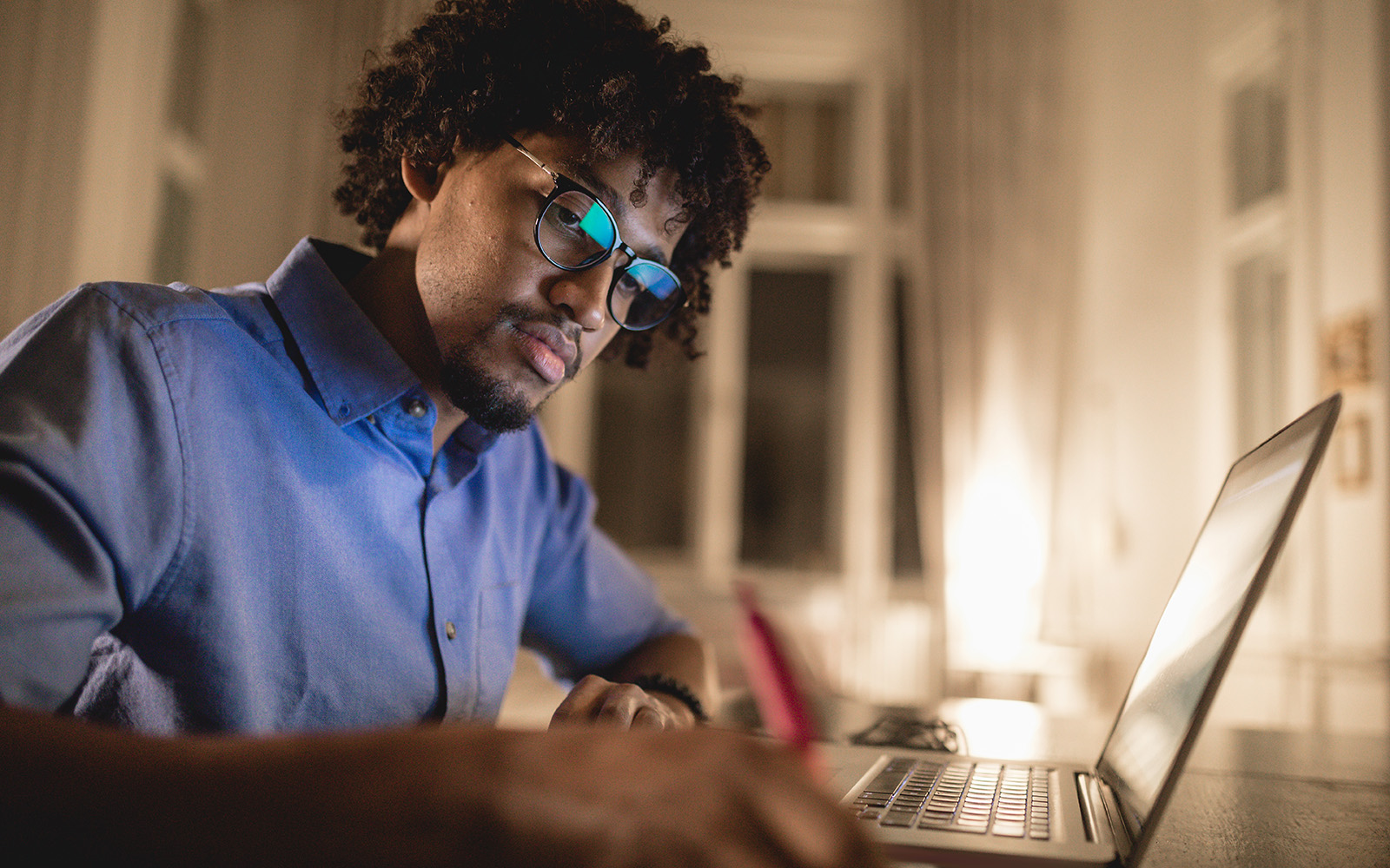 A black student studies at a laptop computer in a home office.