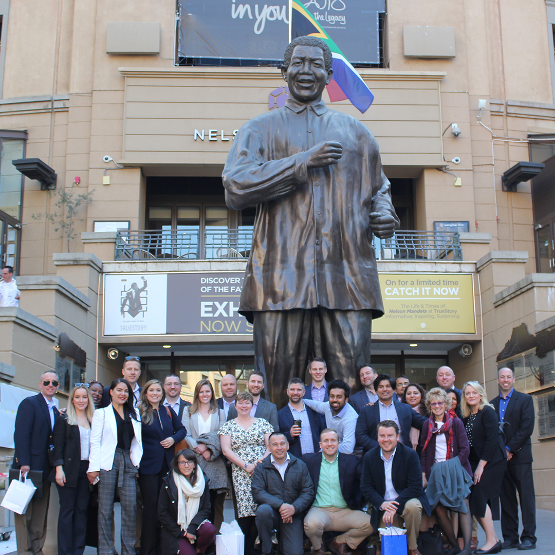 EMBA Class of 2020 posing with statue of Nelson Mandela in Mandela Square in Johannesburg.