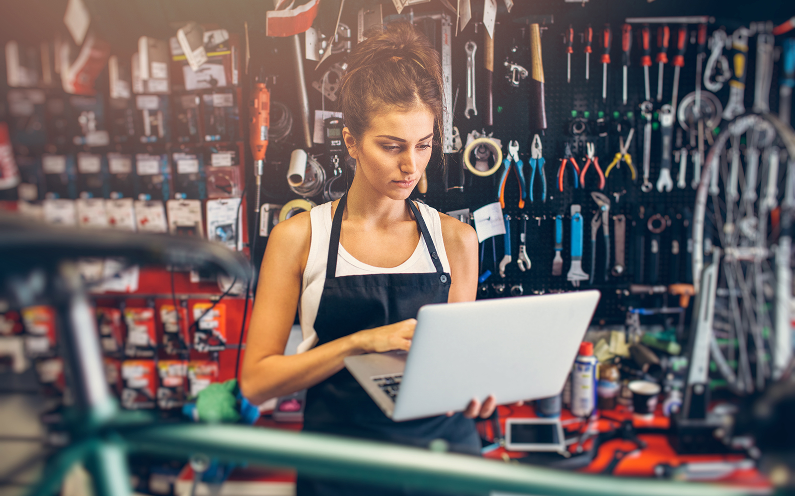 Portrait of a young female bicycle mechanic using a laptop.
