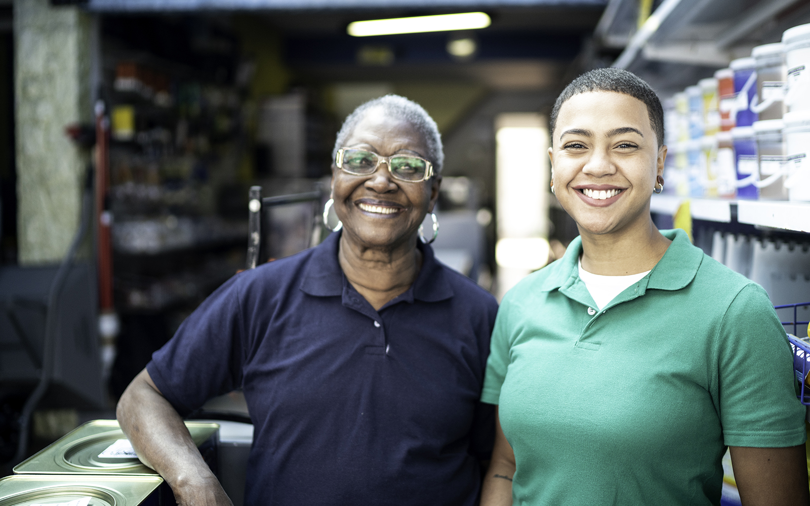 Portrait of mother and daughter working together in a paint store