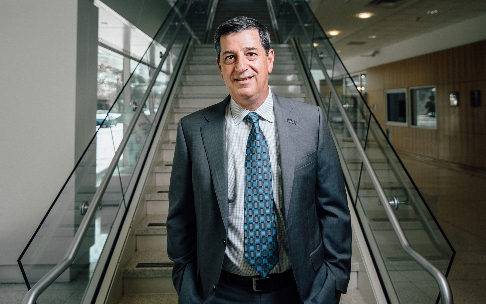 Former Walmart CEO Bill Simon poses in front of an escalator in the UConn Stamford campus.