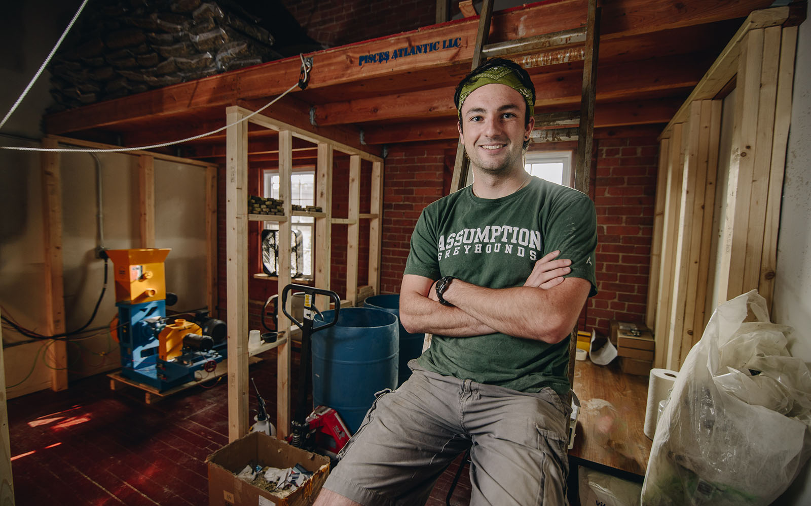 UConn Student Peter Goggins poses in a rustic warehouse.