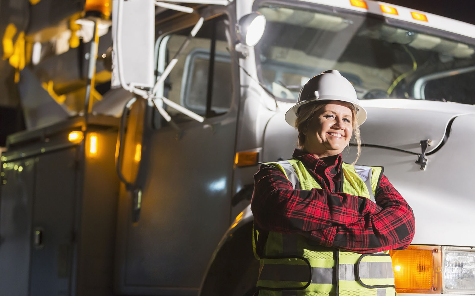A female worker wearing a hardhat and safety vest standing in front of a work truck. She is a utility worker, engineer or technician.