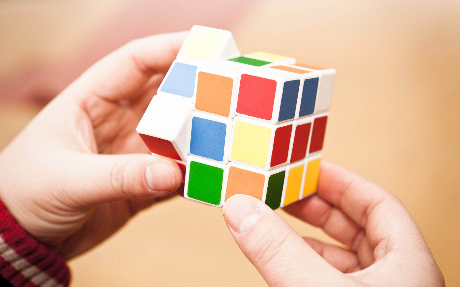 """Shanghai, China - Feb 12, 2012: Hands playing a Rubik's Cube game.Rubik's Cube is a 3D mechanical puzzle invented in 1974 by Hungarian sculptor and professor of architecture Erna Rubik"""