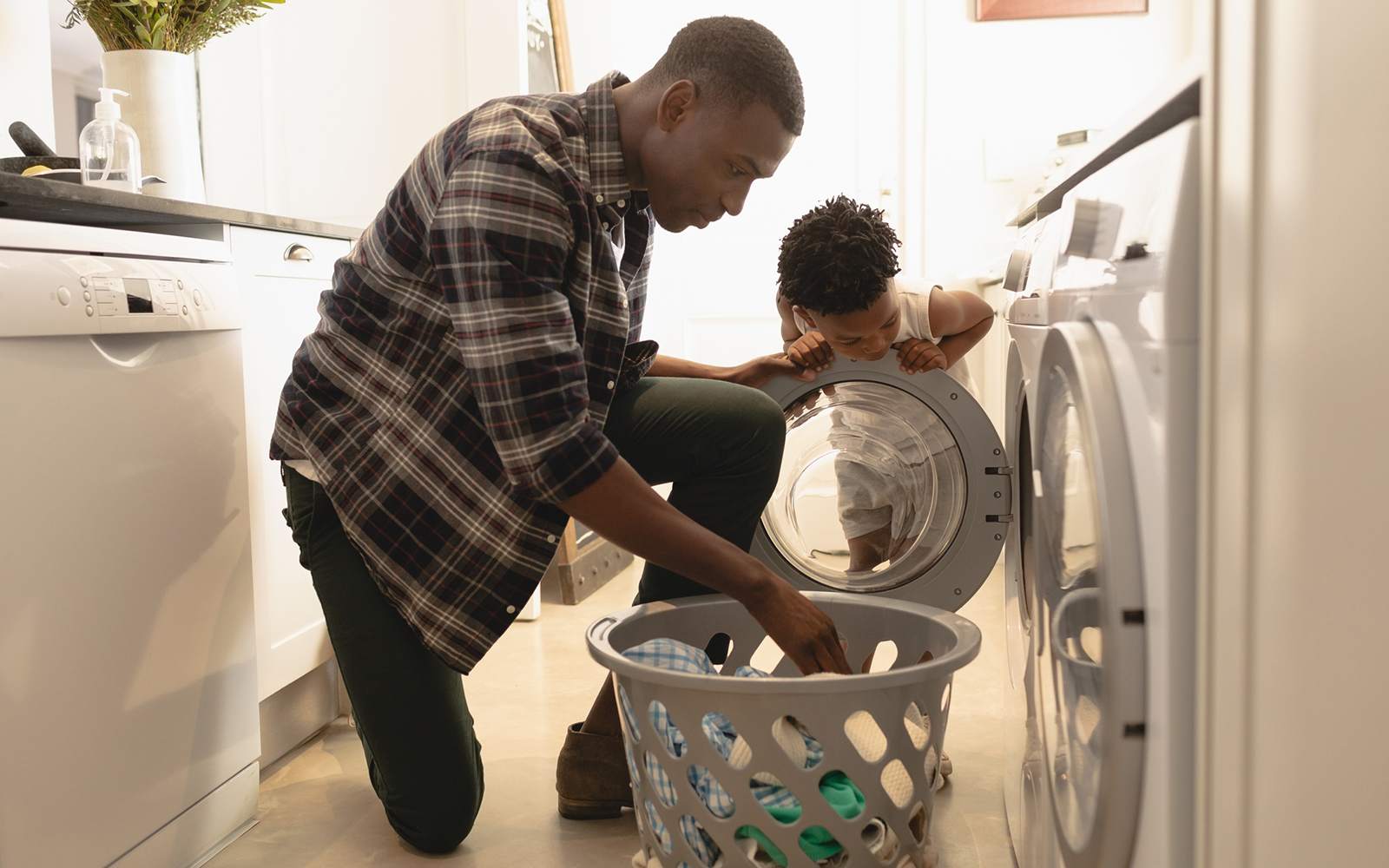Father and son washing clothes in washing machine