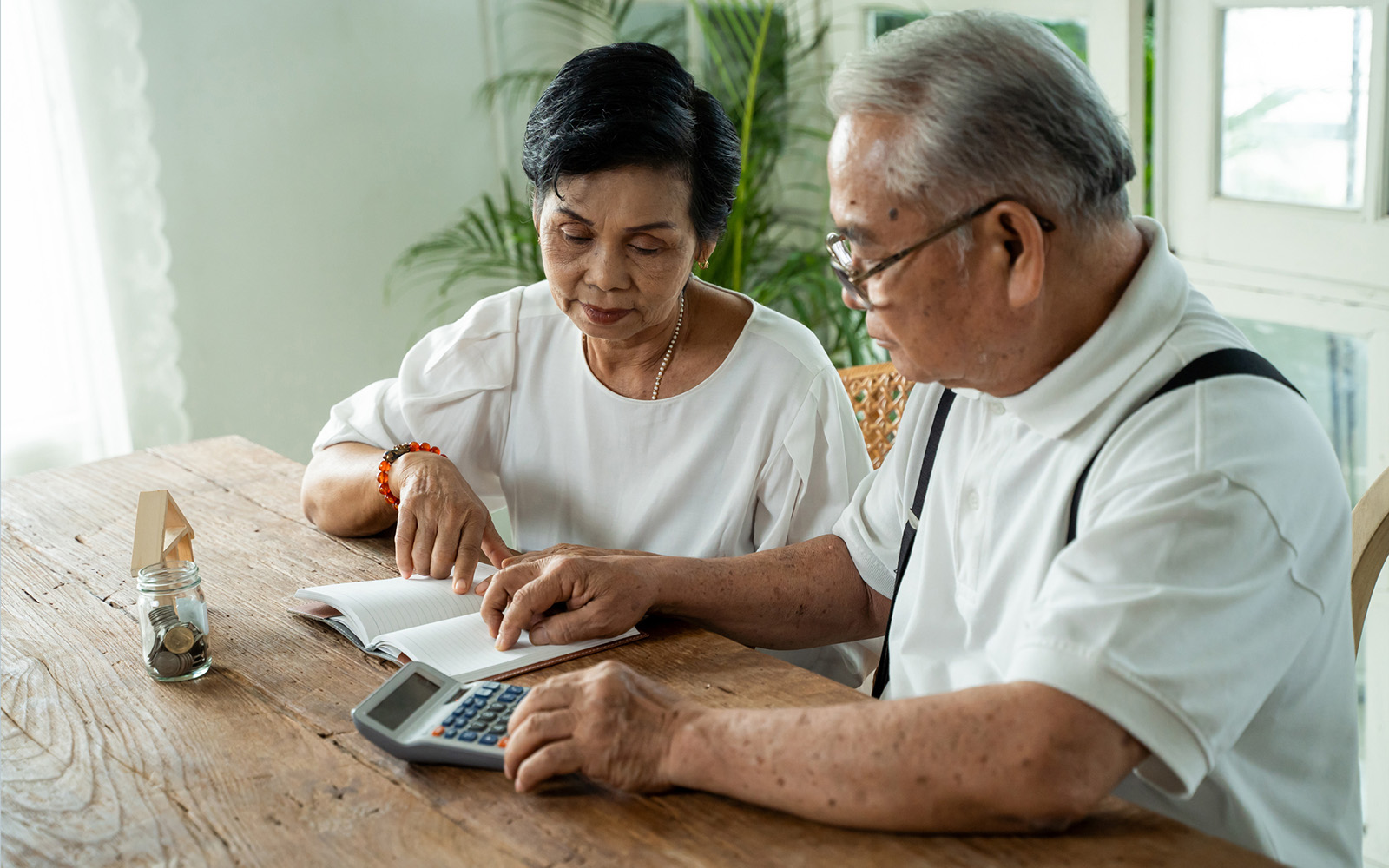 Asian senior couple stressed and serious counting with calculator and having money problem