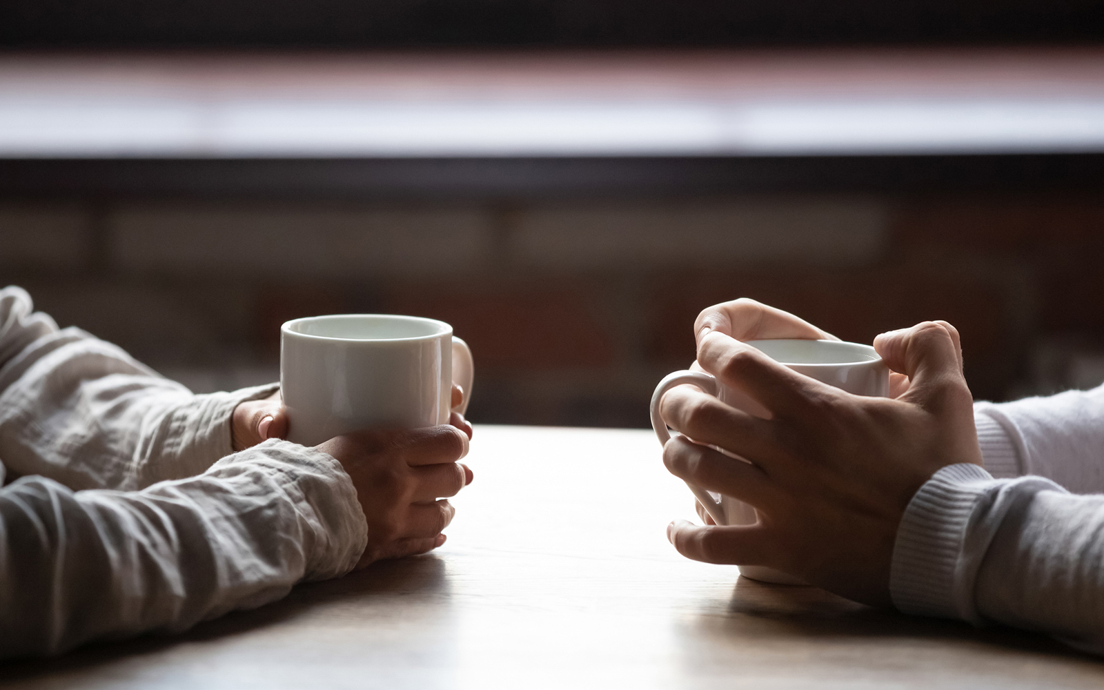 Close up woman and man sitting in cafe, holding warm cups of coffee on table,
